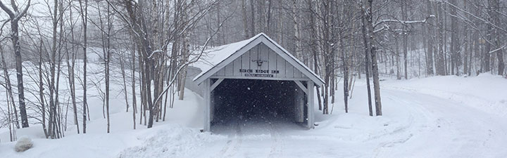 Fresh snow drapes the Covered Carriageway at the Birch Ridge Inn