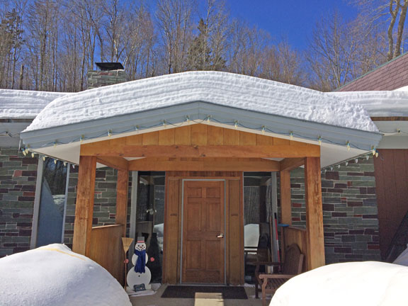 The front portico of the Birch Ridge Inn with layers of snow in it's roof.