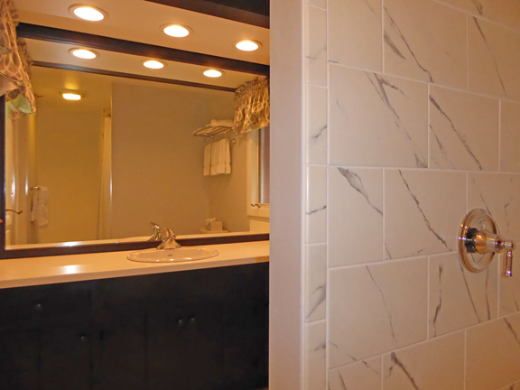 New vanity, light treatment, and carrara marble style tile in Room 2
